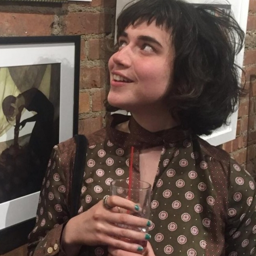 Illustration student Shannon Ryan in front of brick wall covered with framed illustrations, black hair, smiling, brown dress with white circles, holding glass with red straw
