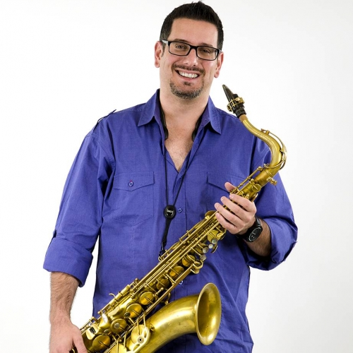 Headshot of Chris Farr with gold-tone tenor saxophone, purple shirt, glasses