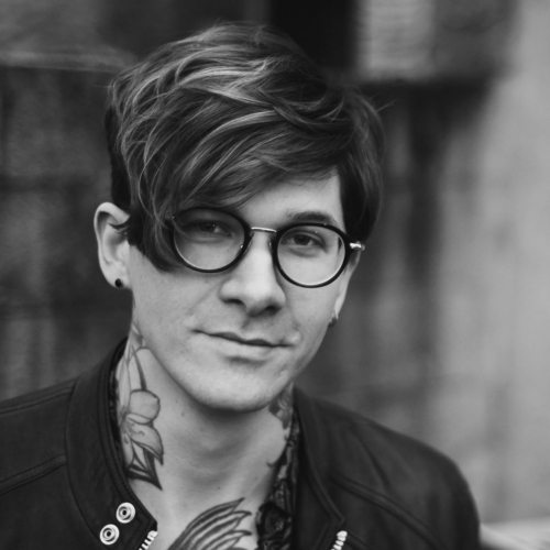 Head shot of Matt McAndrew, black and white, round glasses and neck tattoos