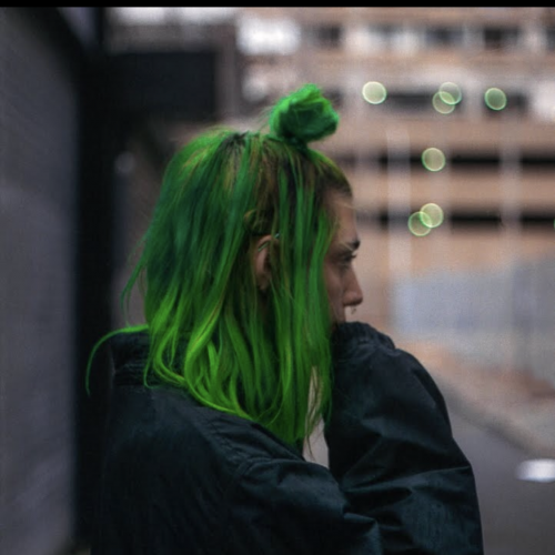 person with green hair wearing a jacket