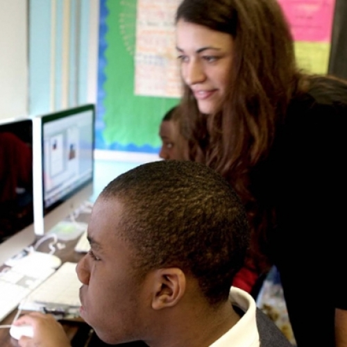 Michele McKeone assisting a student at a computer