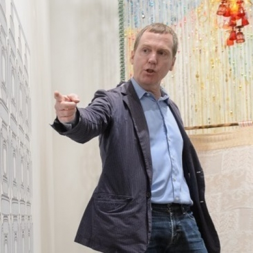 Dan Walsh in gray suit in front of artwork pointing to painting