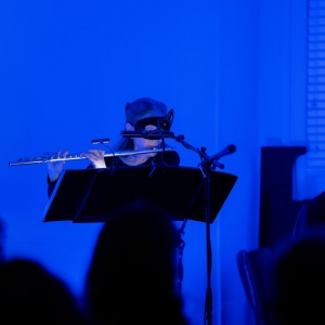 A flutist playing with a black mask on and blue lighting