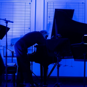 A pianist with a black mask on and blue light surrounding a grand piano