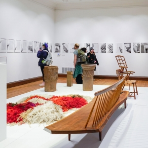 A picture of the Invisible City gallery with a pile high rug and a wooden bench