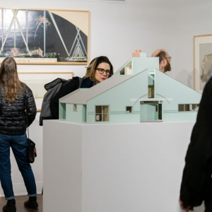 People looking at a model of a house in the Invisible City gallery