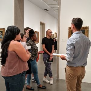 Faculty member Mickey Maley talks to students in front of a piece of art in the Philadelphia Museum of Art.