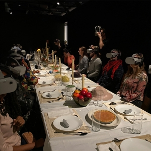 Students sit around a dinner table with virtual reality headgear at Wonderspaces Philadelphia.