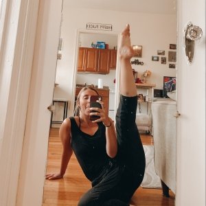 Selfie of Emily through their mirror with leg extended in the air in a dance pose