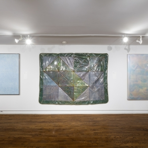 Invisible City Exhibition, Gallery E: a row of three large works on one long wall––one light colored geometric painting, one plastic encased quilt, one pale encaustic work