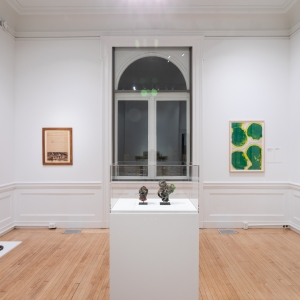 Invisible City Exhibition, Gallery A; view of work in center of room, window behind it, and a piece of work flanking either side of the window