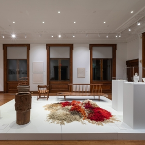 Invisible City Exhibition, Gallery B: raised platform in foreground displaying wooden furniture, pots, vases and a large fiber work  with large windows in the background