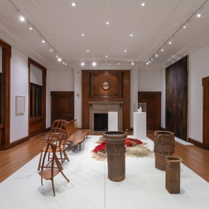 Invisible City Exhibition, Gallery B: raised platform in foreground displaying clay pots and wooden furniture with grand fireplace in background