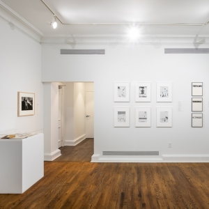 Invisible City Exhibition, Gallery C: group of 6 photographs on far wall next to a column of three photographs; a single photograph is on side wall above a display on a pedestal