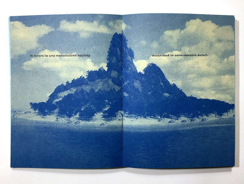 """utopia"" is a printed work by faculty member Sarah Nicholls. It is a book laid open to show a print of an island in blue ink. The text on the pages reads ""it refers to any nonexistent society described in considerable detail"""